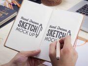 hand-held-moleskine-style-psd-mockup-sketchbook