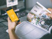 iPhone In Hand, Magazine & Bokeh Laptop Workspace PSD Mockup