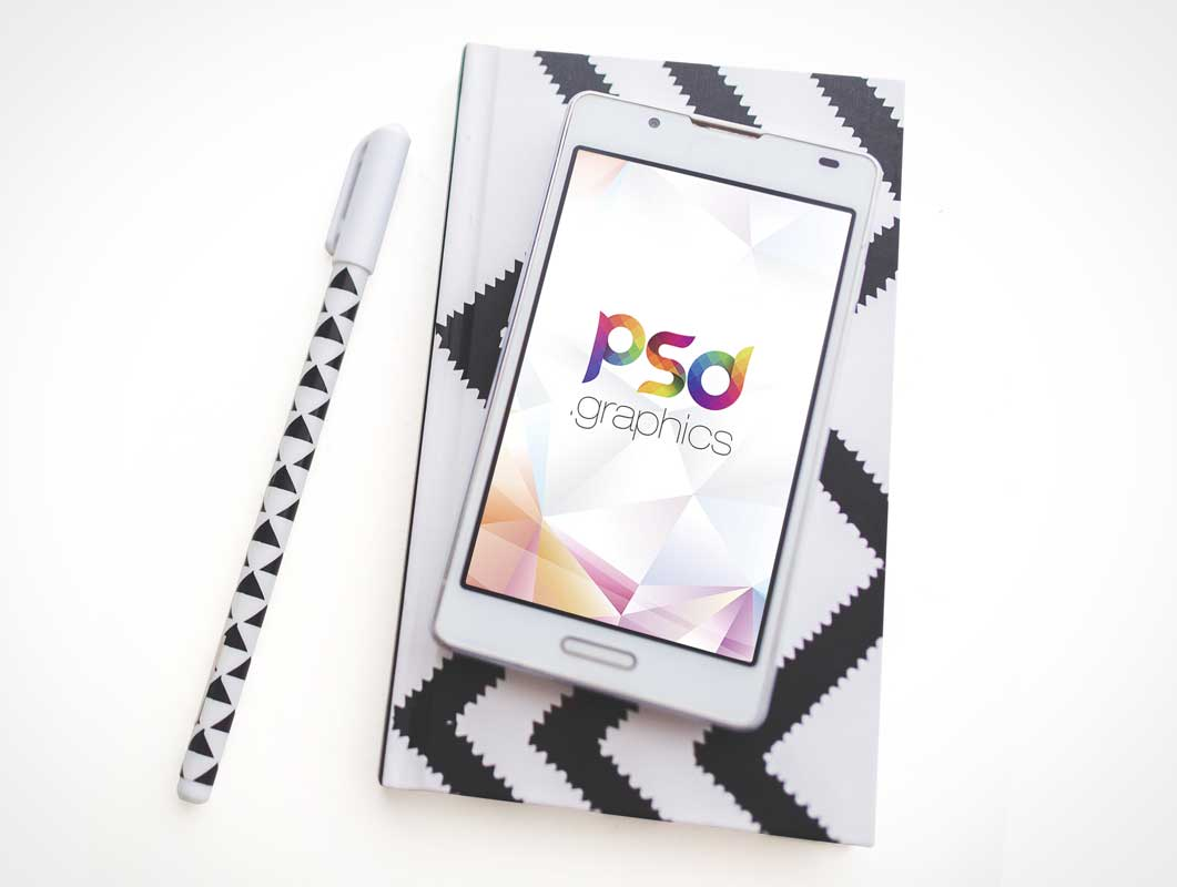 Android Smartphone Display Face Up Over Notebook & Pen PSD Mockup